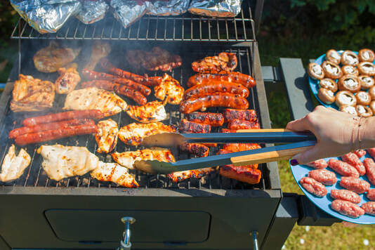 Grilling food on barbecue grill, hands preparing skewers